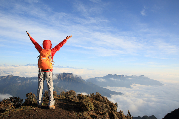 Man on a mountain top celebrating